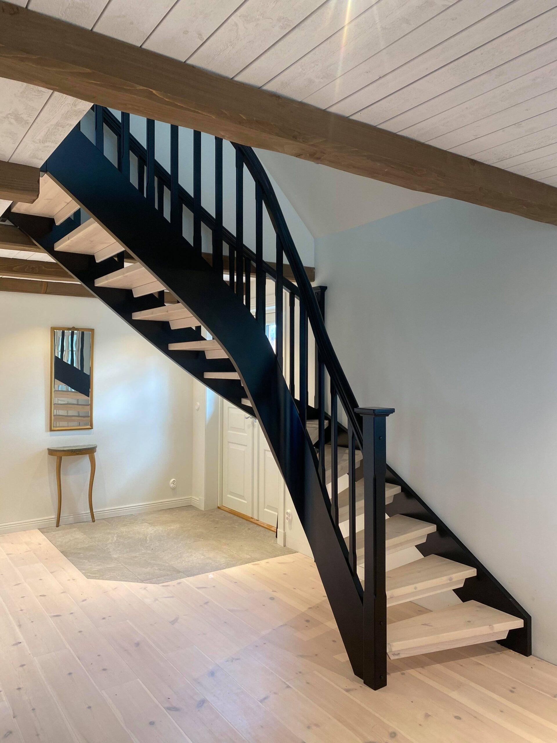 ljusa trästeg i svängd trappa med svart räcke