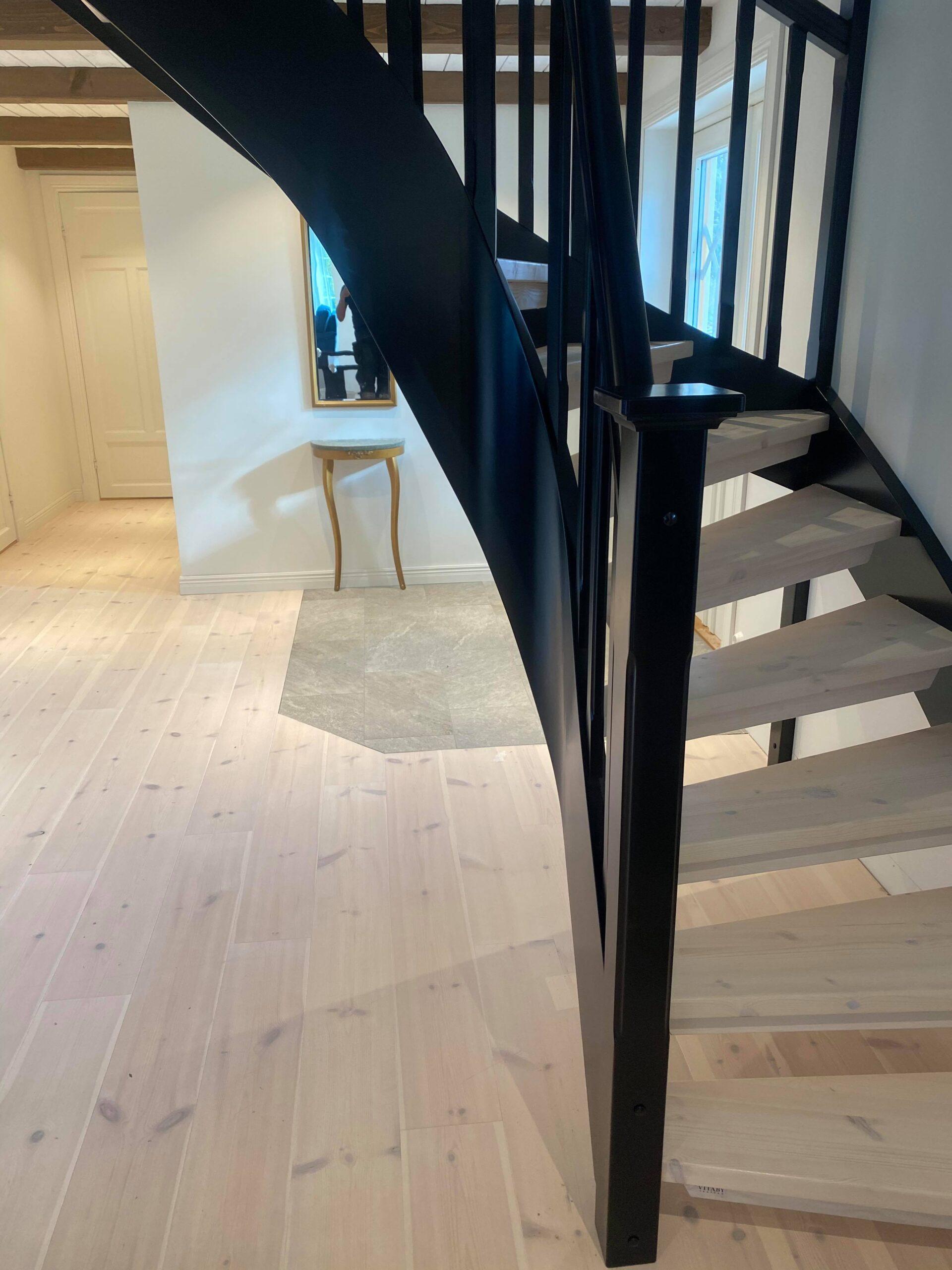 ljus trätrappa med svart räcke, modern