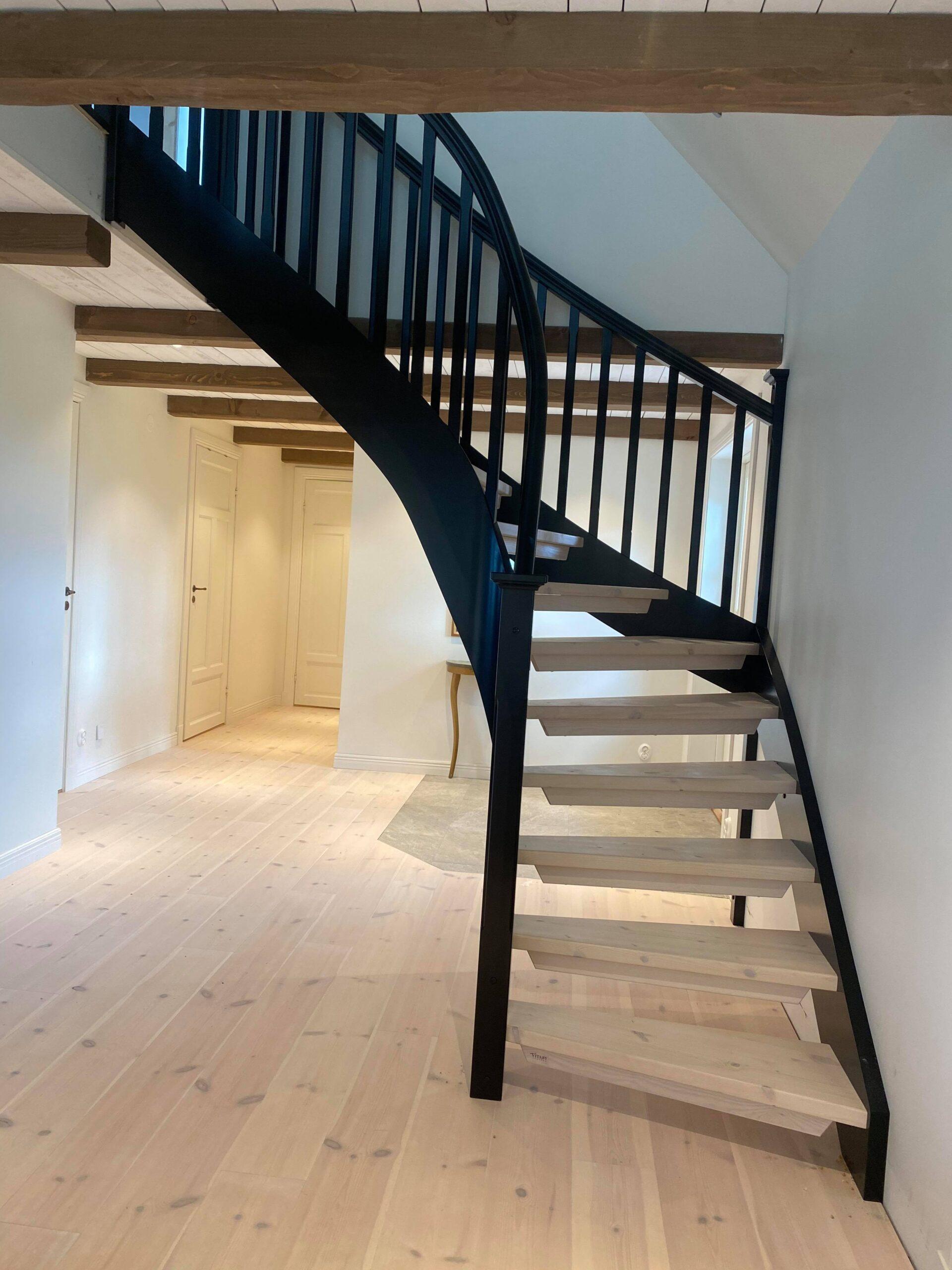 ljus parkett som följer med i trappstegen, trappa med svart räcke