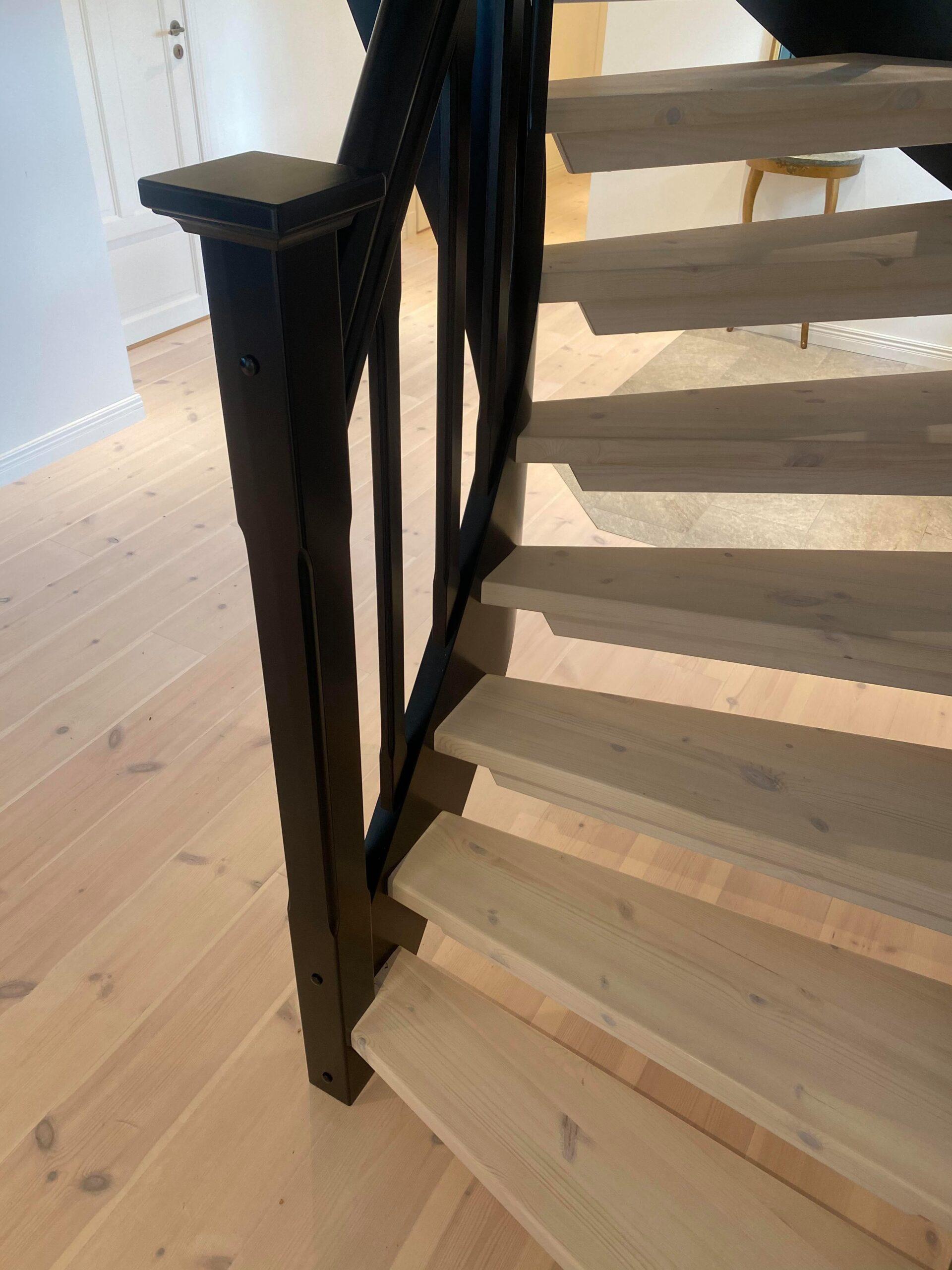 ljus trätrapp, med svart räcke, samma stil som parketten