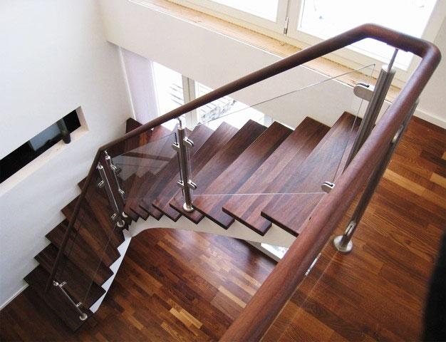 Modern trappa i mörkt trä och med glasväggar.