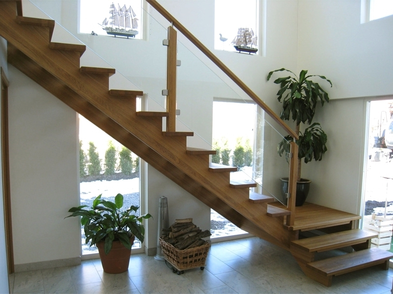 En modern trappa i trä med glasväggar.