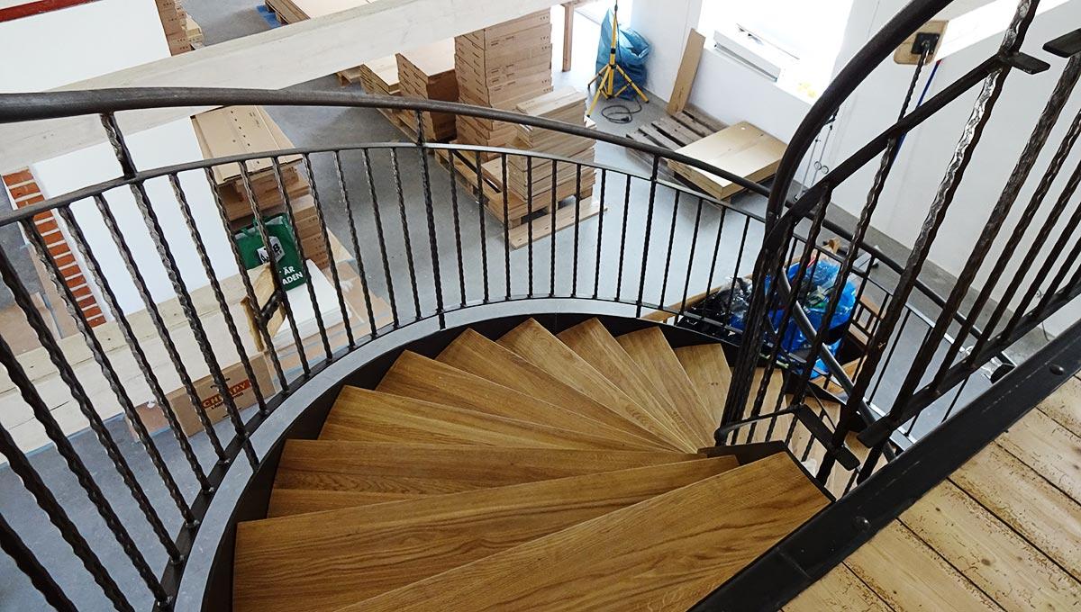 En spiraltrappa med trästeg och svarta räcken inomhus.