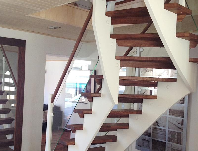 Vit trappa inomhus med trappsteg och handledare i ek.