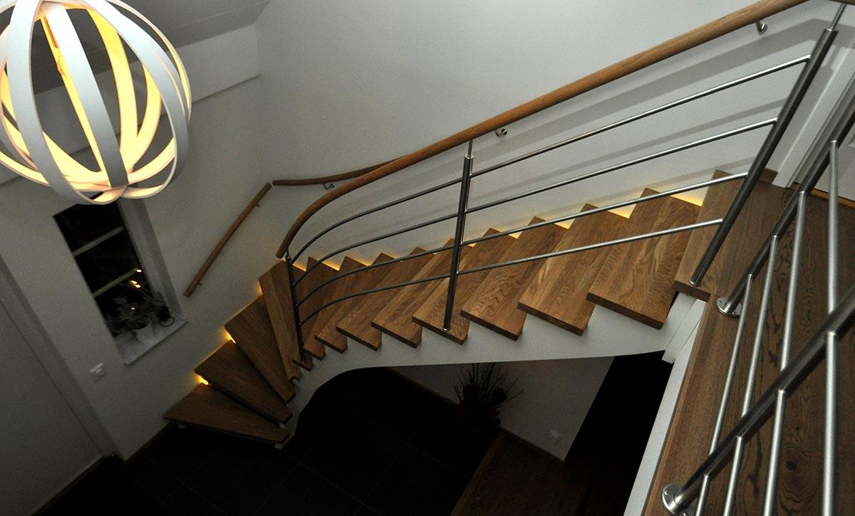 En vit trappa med trappsteg i ek och trappbelysning.