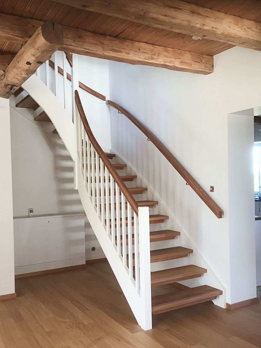Vit trappa inomhus med handledare och trappsteg i ek.