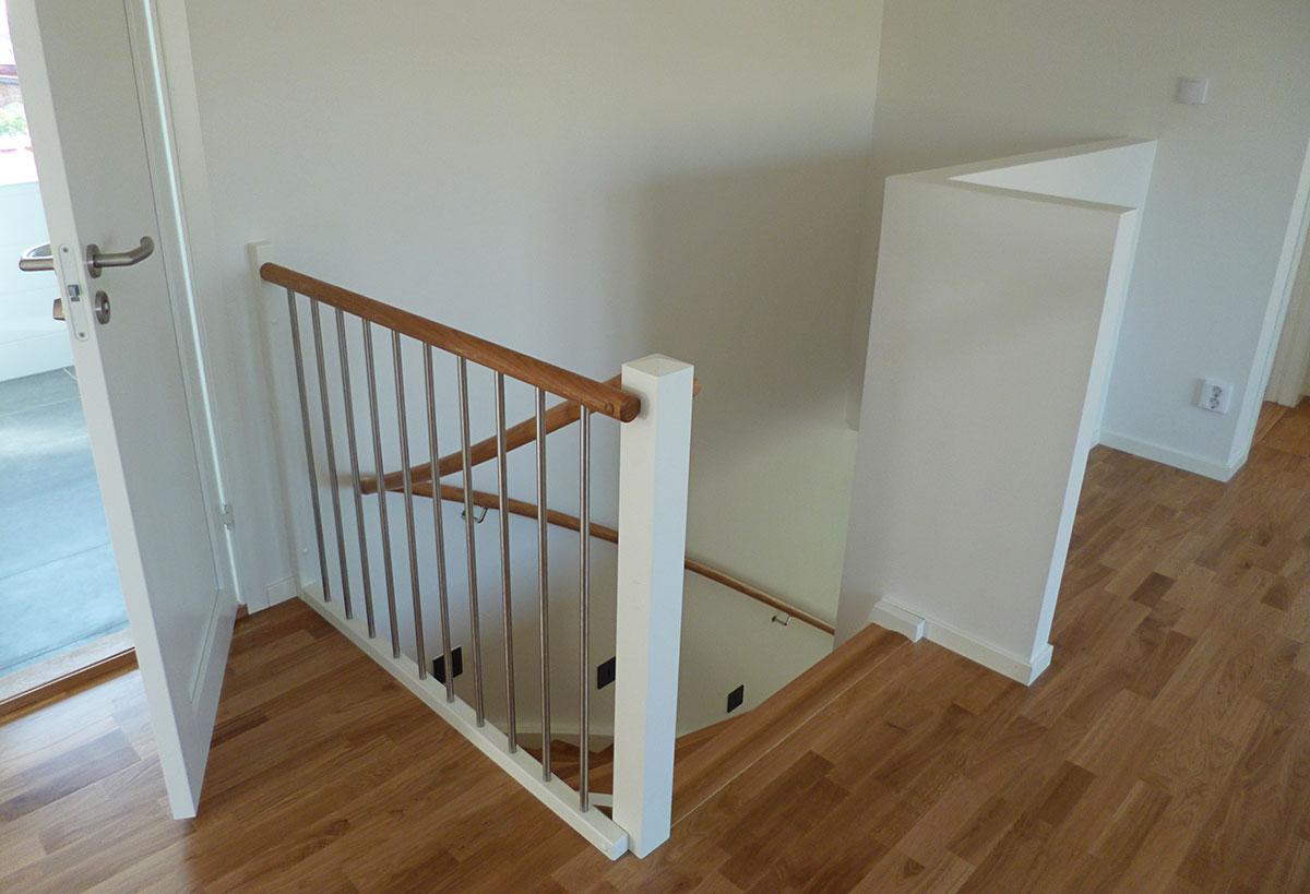 En vit trappa med handledare i ek.